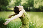 Girl-in-green-with-open-arms-in-green-field-of-grass-300x199